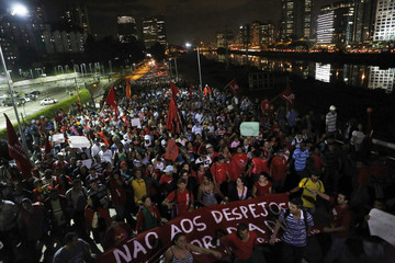Members of Brazil's Homeless Workers' Movement shout slogans as they block the Marginal Pinheiros during a protest against the World Cup in Sao Paulo
