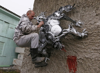 Mechanic and welder Kulagin strengthens the bracing of a spider sculpture, made by Kulagin, during a demonstration on the wall of an automobile repair workshop in the town of Divnogorsk