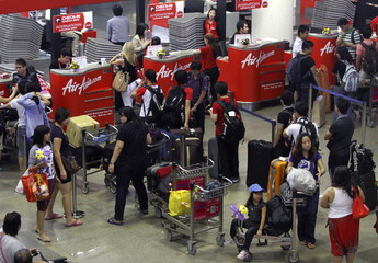 Passengers wait to check in for their flights at Don Muang International Airport in Bangkok