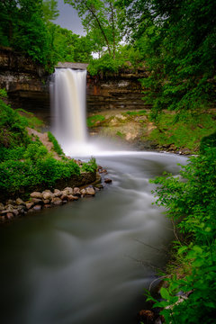 A flowing Minnehaha Falls framed by green trees at dusk