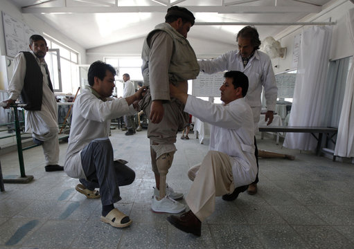 Afghan doctors adjust a prosthetic leg of a man at an ICRC hospital for war victims at the Orthopedic Center of the International Committee of the Red Cross in Kabul