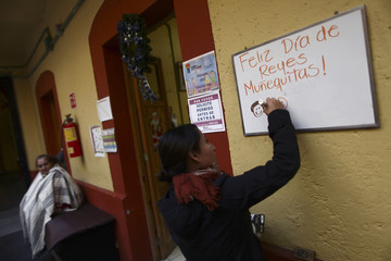 """A volunteer writes """"Happy Three Kings Day little dolls!"""" on a whiteboard during a Three Kings Day celebration at Casa Xochiquetzal, a shelter for female sex workers, in Mexico City"""