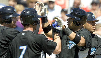 Ruiz is congratulated by team mates Reed and Hill after he hit a grand slam off Bonderman in the second inning of their MLB baseball Grapefruit League spring training game in Dunedin