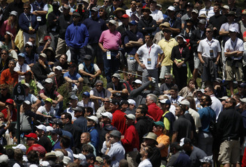 Woods (C) of the U.S. is obscured by a large crowd surrounding the sixth tee uring the first round for the 2012 U.S. Open golf tournament on the Lake Course at the Olympic Club in San Francisco