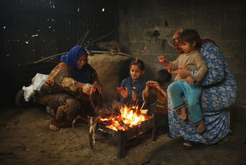 Members of a Palestinian family warm themselves by a fire on rainy day in the northern Gaza Strip