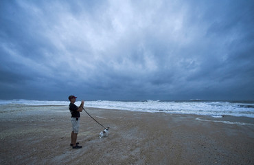 Local resident Carroll photographs storm surf with his dog, Willy, in St. Augustine Beach, Florida, as Tropical Storm Sandy, downgraded overnight, passes offshore