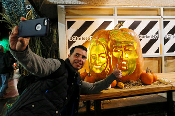 A man takes a selfie next to a giant pumpkin with the faces of 2016 Democratic nominee Hillary Clinton and Republican presidential nominee Donald Trump in New York