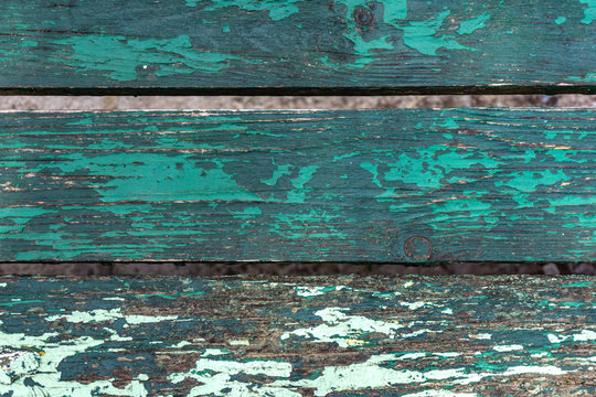 Close-up of a bench, look from above. Suitable for texture, background. Vintage green and turquoise with dull paint, nostalgia.