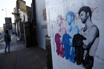 A pedestrian looks at a mural depicting singer George Michael, in London