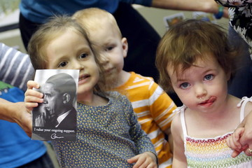 A little girl holds a picture of Obama to show him as he visits her classroom after his remarks on Jewish American History Month at the Adas Israel Congregation synagogue in Washington