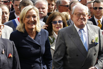France's far right National Front political party leader Marine Le Pen and her father Jean-Marie Le Pen (R) attend the National Front's annual May Day rally in Paris