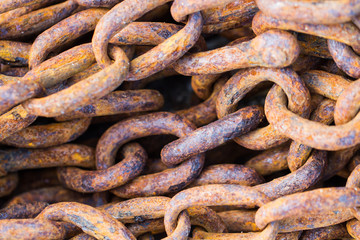 A full frame image of thick, heavy industrial chains that are rusty, weather and worn an industry background image.