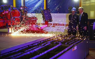 Britain's Defence Secretary Michael Fallon watches as the first piece of steel for the successor submarine programme is cut at the BAE systems facility at Barrow-In-Furness