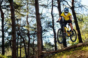 Professional Cyclist in Yellow T-shirt and Helmet Riding the Mountain Bike in Forest. Extreme Sport Concept.