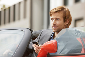 Business man on phone in an electric car