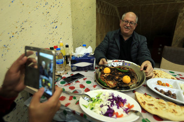 People take pictures of a meal of roasted carp at a restaurant named Trump Fish in the Kurdish city of Duhok