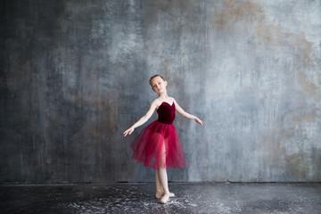 girl ballerina in red tutu doing exercise