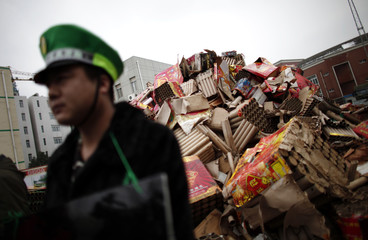 People who are representing companies, which Chinese multimillionaire Chen Guangbiao claims pollute the environment, parade in front of discarded firework packaging during an event in Nanjing