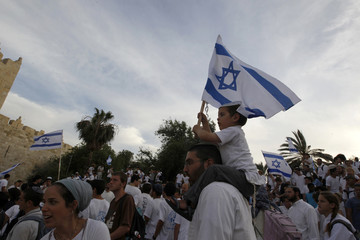 Israelis carry flags as they walk outside Jerusalem's Old City during a parade marking Jerusalem Day