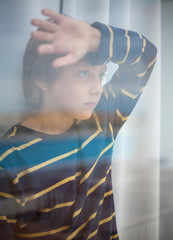 Boy looking through glass of window