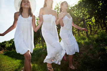 Mother and daughters running in vineyard