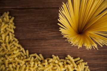 Dry pasta with ingredients on a old wood