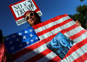 A woman holds a U.S. national flag with a picture depicting to U.S. President Trump during a protest outside the U.S. Embassy in Buenos Aires