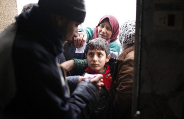 A Syrian refugee boy waits in a queue to receive bread from Turkish humanitarian agencies, at Bib Salam refugee camp in Syria near the Turkish border
