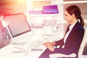 Composite image of smiling businesswoman working on computer