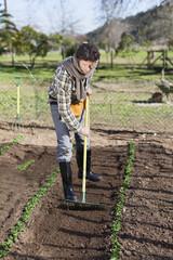 Man turning over soil in garden