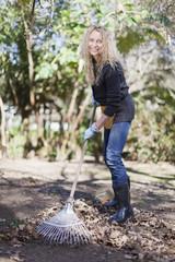 Smiling woman raking leaves outdoors