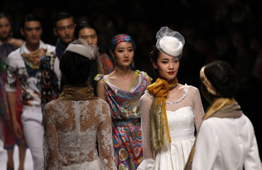 Models present creations by WOO during Shanghai Fashion Week