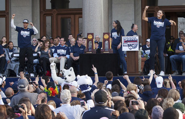 University of Connecticut basketball players Shabazz Napier and Stefanie Dolson lead the crowd in a cheer during the UConn Victory Parade and Rally in Hartford, Connecticut