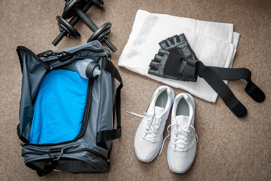 Fitness equipment and working out concept with dumbbells, gym bag, white towel, running shoes, workout gloves and water bottle