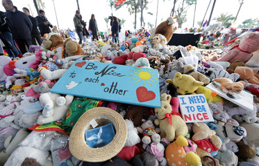 Victims' relatives and members of victims' associations collect in boxes the flowers, drawings and toys left by passers-by at a memorial for the victims of the July 14 fatal truck attack on the Promenade des Anglais in Nice