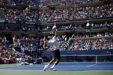 Novak Djokovic of Serbia serves to Paul-Henri Mathieu of France during their match at the 2014 U.S. Open tennis tournament in New York