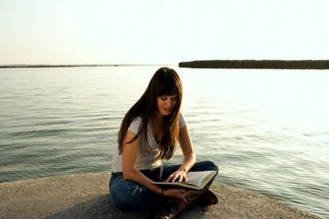 Girl reading by lake