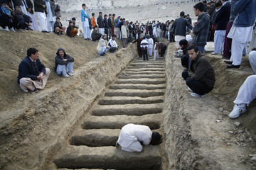 A man prepares graves for the burial of victims of Saturday's bomb attack in a Shi'ite Muslim area, in the Pakistani city of Quetta