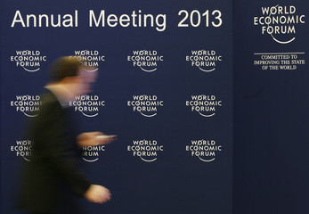 A man walks past the logo of the WEF inside the Congress Hall at the Swiss Alpine resort of Davos