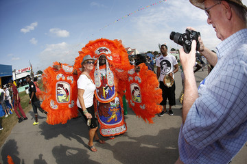 A festival goer has her photo taken with a Mardi Gras Indian during the New Orleans Jazz and Heritage Festival in New Orleans