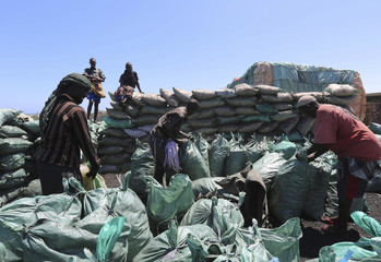 People work on a consignment of charcoal destined for the export market in Barawe