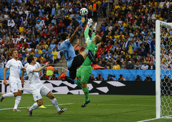 England's goalkeeper Hart makes a save next to Uruguay's Caceres during their 2014 World Cup Group D soccer match in Sao Paulo