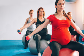 Group of pregnant women exercising and lifting weights feeling strong