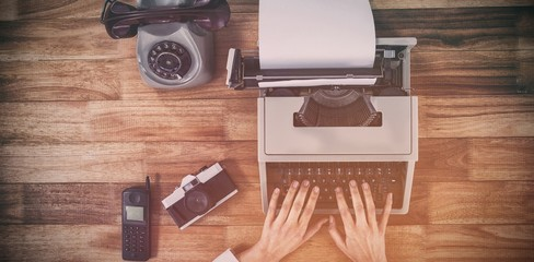 Businesswoman typing on typewriter by vintage camera and phone