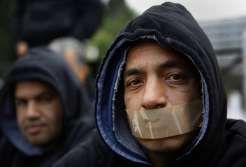 A Syrian refugee, with tape across his mouth, join others in a protest for a sixth consecutive day in Athens