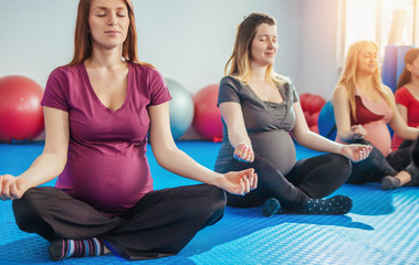 Group of pregnant women meditating on yoga class in lotus posture