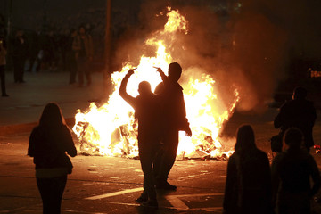 A demonstrator gestures as they gather around a burning barricade in Santiago city