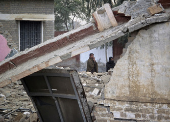 Residents stand amidst the rubble of a school which was hit by explosives in the outskirts of Dera Ismail Khan