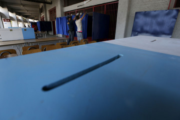Workers arrange voting booths at the National Stadium which will be used as a voting station for the upcoming presidential elections in Santiago