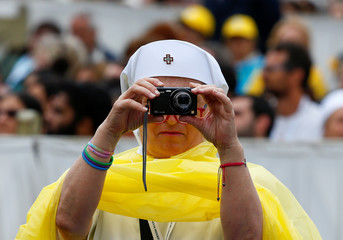 A Red Cross member takes a picture as Pope Francis celebrates a mass during a Jubilee for the sick and disabled in Saint Peter's Square at the Vatican